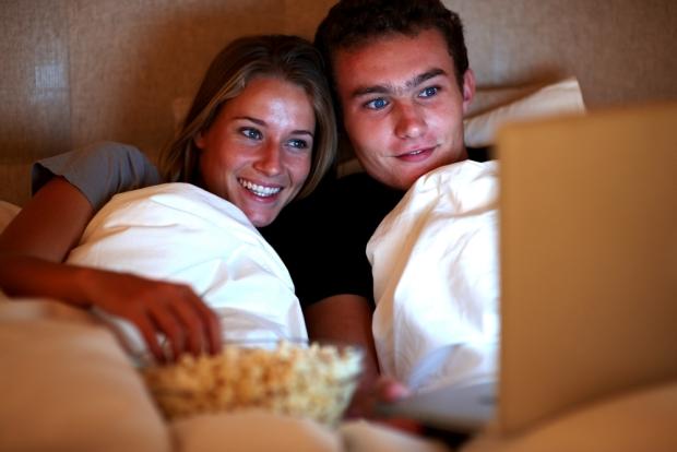 Una pareja en la cama viendo una película erótica